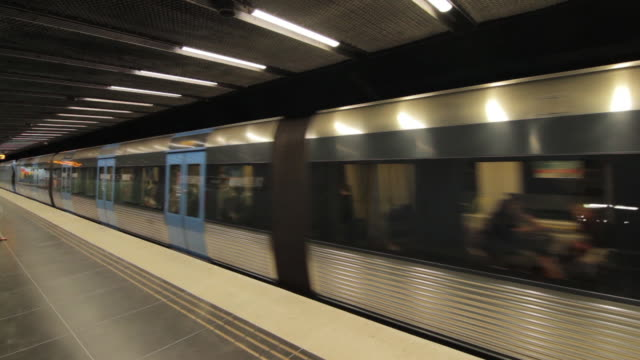 Panning shot of a train pulling into a station on Stockholm's metro network.