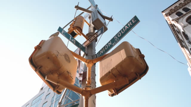 panning shot of a union square street sign in new york city - verkehrs leuchtsignal stock-videos und b-roll-filmmaterial
