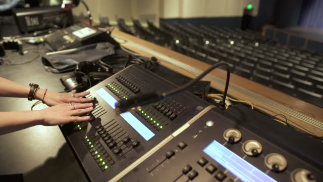 panning shot of a woman adjusting a mixing console - conference centre stock videos & royalty-free footage