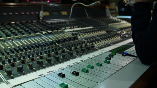 vidéos et rushes de panning shot of an analogue sound mixing desk in action - mixage du son