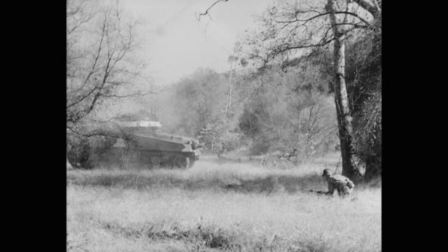 panning shot of army soldiers with armored tank on military operation in grassy field - 戦車点の映像素材/bロール