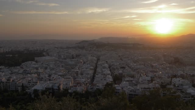 Panning shot of Athens and the Acropolis from path on Mount Lycabettus at sunset, Athens, Greece, Europe
