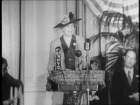 Panning shot of audience sitting / Eleanor Roosevelt stands at podium on stage with flags in background gives speech / closeup of Roosevelt at podium...