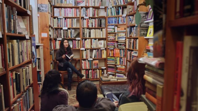 panning shot of author event in bookstore - author stock videos & royalty-free footage