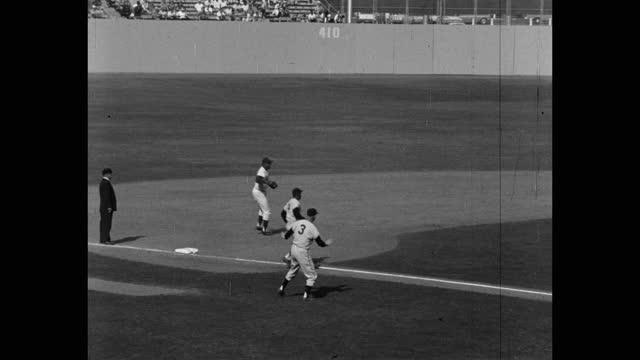panning shot of baseball player hitting ball and running on baseball diamond, dodger stadium, los angeles, california, usa - 野球用グローブ点の映像素材/bロール