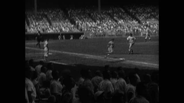 panning shot of baseball player hitting, running bases during game, yankee stadium, new york city, new york, usa - 野球用グローブ点の映像素材/bロール
