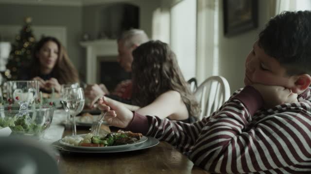 panning shot of bored boy picking at food during christmas dinner / orem, utah, united states - sadness stock videos & royalty-free footage