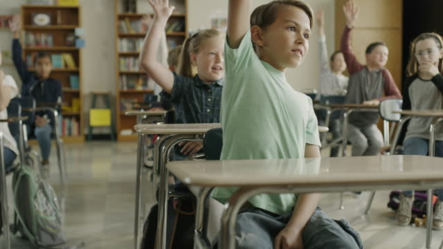 panning shot of boy raising hand and answering question in classroom / provo, utah, united states - arme hoch stock-videos und b-roll-filmmaterial