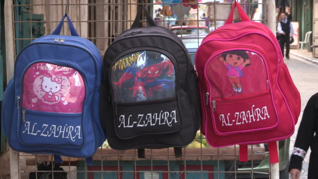Panning shot of branded children's backpacks and foot traffic