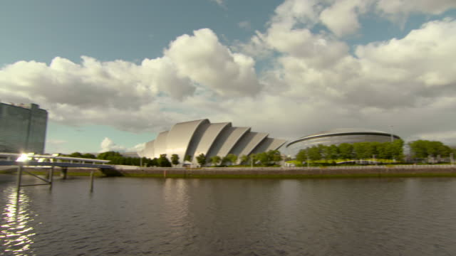panning shot of bridge over river clyde by famous landmarks in city against sky - glasgow, scotland - auditorium stock videos & royalty-free footage
