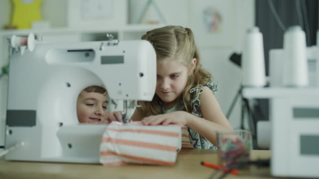 panning shot of brother watching sister using sewing machine / lehi, utah, united states - lehi stock videos & royalty-free footage