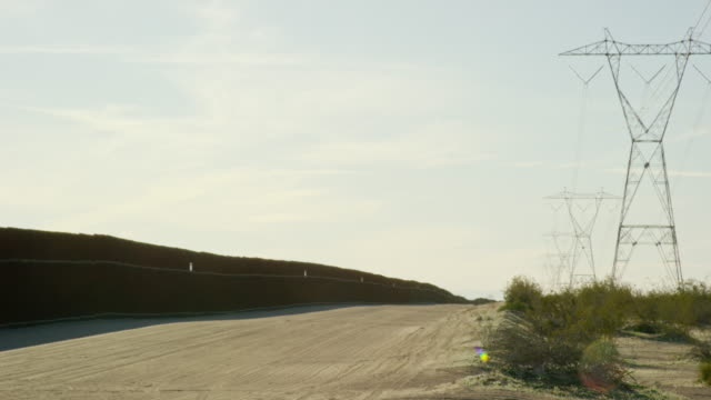 panning shot of bushes and power lines on the right and the steel-slat border wall (on the us side) between mexico and the united states on a hazy day - international border barrier stock videos & royalty-free footage