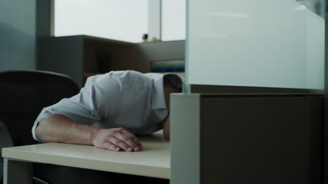 panning shot of businessman in office cubicle sleeping face down on desk / pleasant grove, utah, united states - napping stock-videos und b-roll-filmmaterial