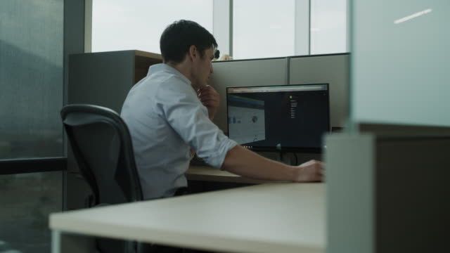 panning shot of businessman in office cubicle using computer / pleasant grove, utah, united states - コンピュータハードウェア点の映像素材/bロール