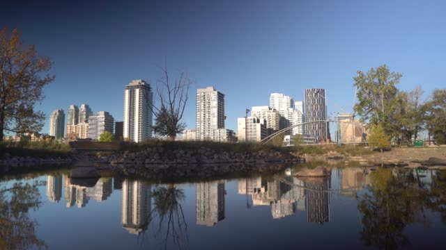 panning shot of calgary skyline reflected onto a pond - calgary stock videos & royalty-free footage