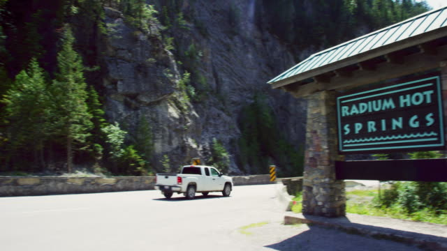 """panning shot of cars and other vehicles driving by a sign for """"radium hot springs"""" in the canadian rockies in british columbia, canada on a sunny day - welcome sign stock videos & royalty-free footage"""