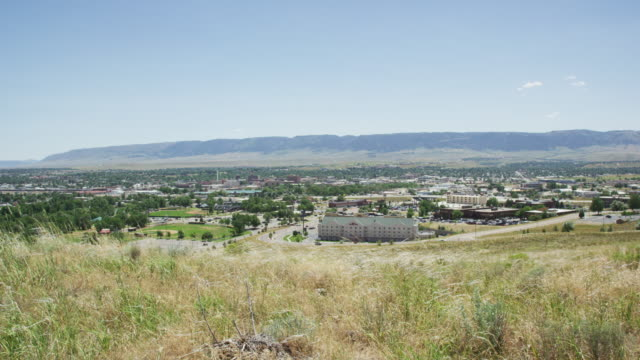 panning shot of casper, wyoming from a grassy hill on a sunny day under a blue sky - wyoming stock videos & royalty-free footage