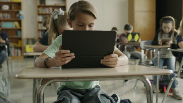 Panning shot of children in classroom reading digital tablets / Provo, Utah, United States