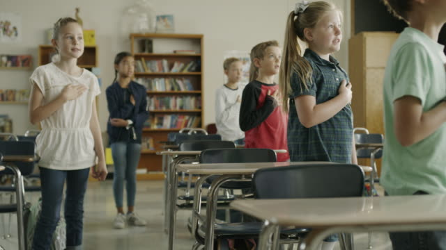 panning shot of children reciting pledge of allegiance in school classroom / provo, utah, united states - amerikanischer treueschwur stock-videos und b-roll-filmmaterial