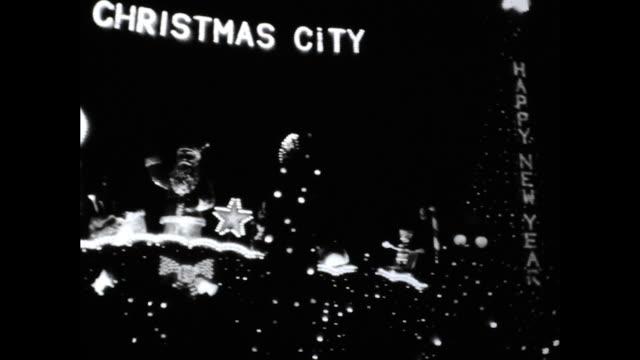vídeos y material grabado en eventos de stock de panning shot of christmas trees and christmas decorations in the dark lights spelling merry christmas happy new year and the christmas city - ortografia