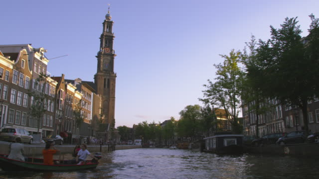 """AMSTERDAM, NETHERLANDS - CIRCA 2013: Panning shot of Clock Tower and other buildings at the canal on 2013 in Amsterdam, Netherlands"""