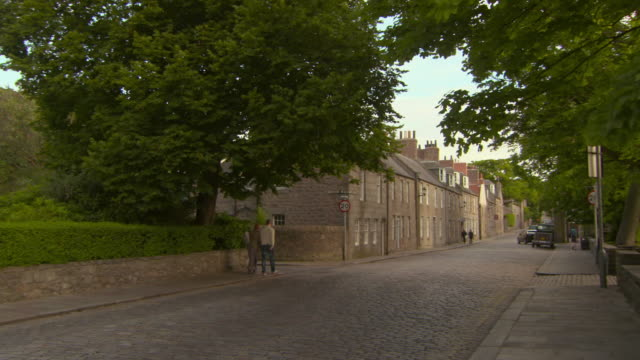 panning shot of cobblestone street by buildings in town against sky - aberdeen, scotland - cobblestone stock videos & royalty-free footage