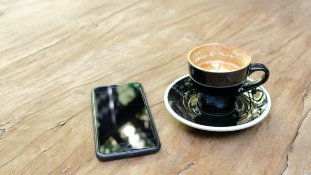 コーヒー カップとモバイル カフェに木製のテーブルの上のショットをパン - カフェイン分子点の映像素材/bロール