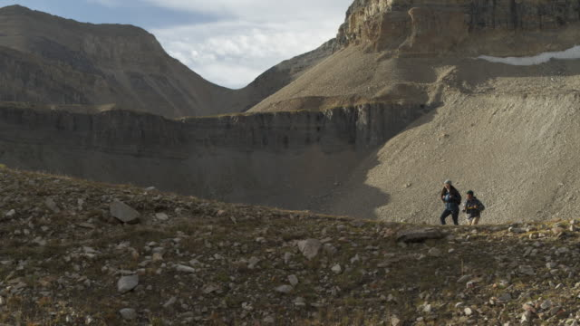 Panning shot of couple climbing hill in mountain range / Mount Timpanogos, Utah, United States