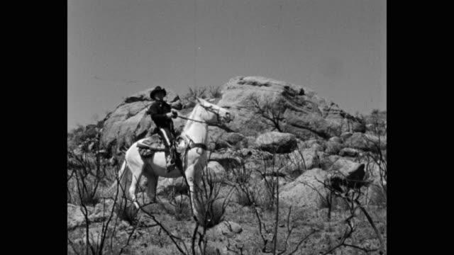 stockvideo's en b-roll-footage met panning shot of cowboy riding horse on rocky hill - alleen één mid volwassen man