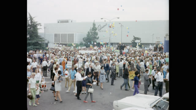 panning shot of crowd with balloons and placards walking on street during political rally of richard nixon - baby girls stock videos & royalty-free footage