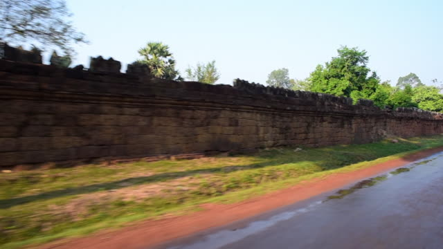 panning shot of damaged surrounding stone wall by wet road against sky - siem reap, cambodia - surrounding wall stock-videos und b-roll-filmmaterial