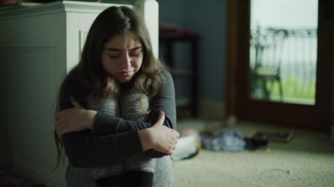 vídeos y material grabado en eventos de stock de panning shot of depressed girl sitting on floor and crying / cedar hills, utah, united states - niñas