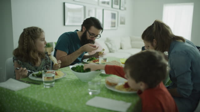 panning shot of family eating at dinner table / lehi, utah, united states - tischtuch stock-videos und b-roll-filmmaterial