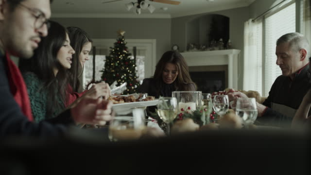 vidéos et rushes de panning shot of family serving and sharing food at christmas dinner / orem, utah, united states - repas