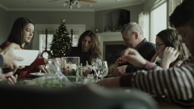 panning shot of family serving and sharing food at christmas dinner / orem, utah, united states - orem stock videos & royalty-free footage