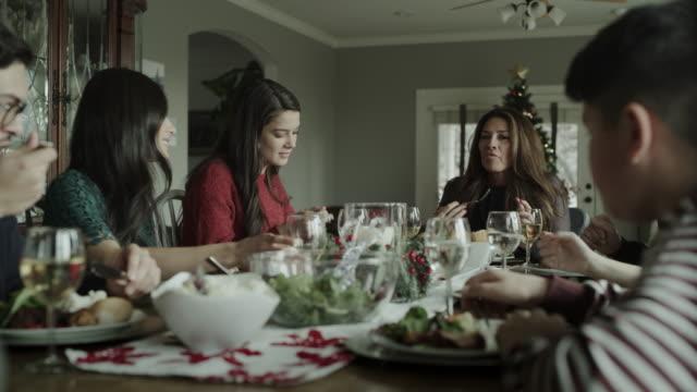 panning shot of family talking and eating christmas dinner / orem, utah, united states - orem stock videos & royalty-free footage