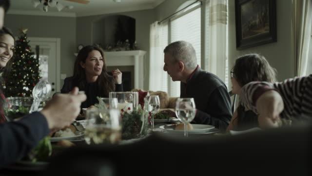 panning shot of family talking and eating christmas dinner / orem, utah, united states - orem utah stock videos & royalty-free footage