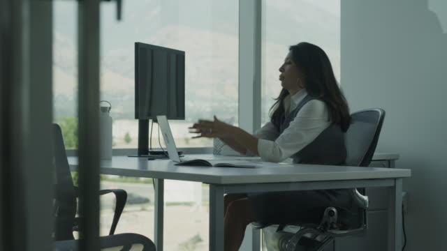 Panning shot of fatigued businesswoman using laptop in office / Pleasant Grove, Utah, United States