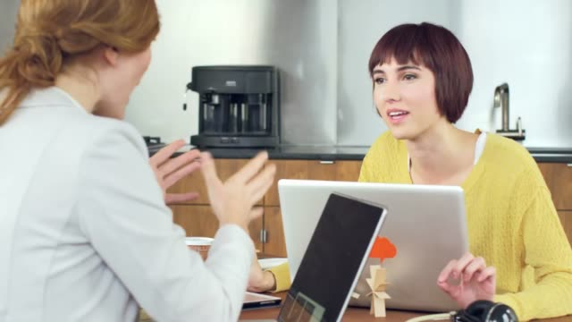 Panning shot of female photo editors discussing at desk in creative office
