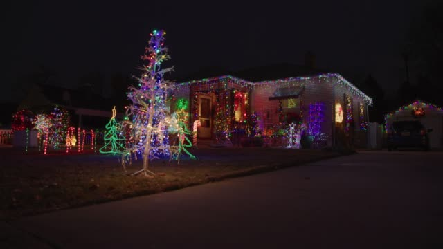 vidéos et rushes de panning shot of festive house with christmas decorations illuminated at night / american fork, utah, united states - guirlande lumineuse décoration de fête