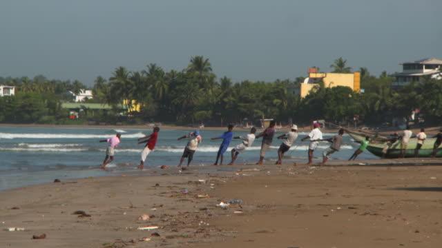 panning shot of fishermen pulling rope at beach against sky on sunny day - arugam bay, sri lanka - sri lanka people stock videos & royalty-free footage