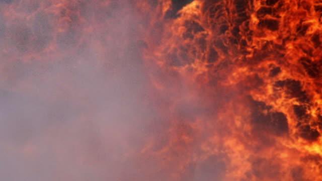 schwenkschuss der flamme mit gebäude- und wasserspritzen aus demfeuerwehrschlauch - fire hose stock-videos und b-roll-filmmaterial