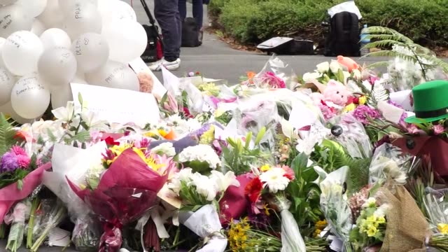 Panning shot of floral tributes near the Al Noor Mosque in Christchurch New Zealand after a white supremacist terrorist committed a mass shooting...