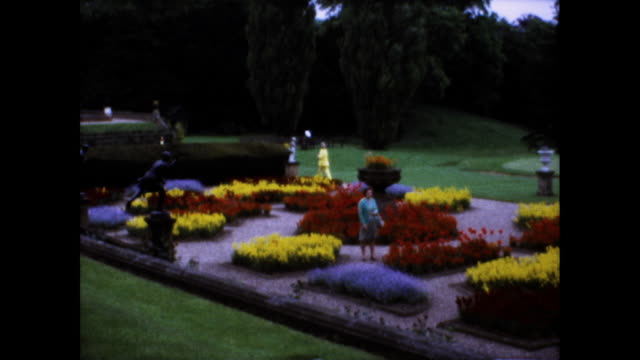 panning shot of garden full of flowers with small sculptures on the side; people scattered among the flowers; lawn and trees in the background - flower stock videos & royalty-free footage