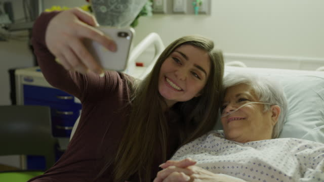 stockvideo's en b-roll-footage met panning shot of girl and grandmother posing for cell phone selfie in hospital bed / salt lake city, utah, united states - zelfportret fotograferen
