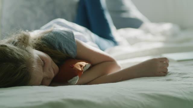 panning shot of girl napping on bed / pleasant grove, utah, united states - 横向きに寝る点の映像素材/bロール