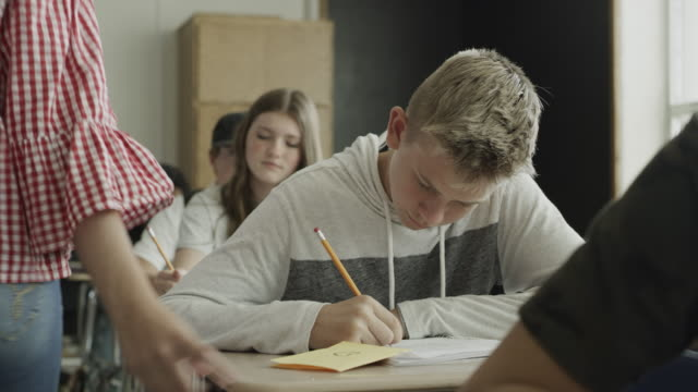 panning shot of girl passing love note to boy in school classroom / provo, utah, united states - text stock-videos und b-roll-filmmaterial