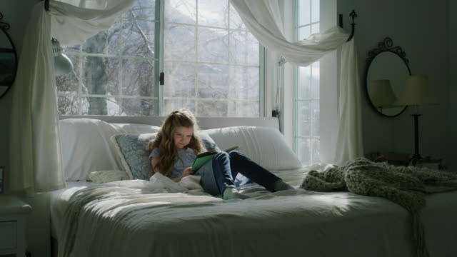 panning shot of girl sitting in bed reading book near bay window / pleasant grove, utah, united states - bay window stock videos & royalty-free footage