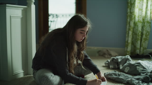 panning shot of girl sitting on floor writing in notebook and texting on phone / cedar hills, utah, united states - picking up stock videos & royalty-free footage