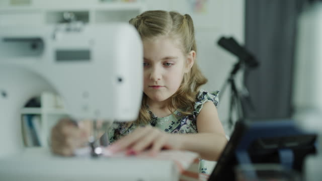 vídeos de stock e filmes b-roll de panning shot of girl watching digital tablet learning to use sewing machine / lehi, utah, united states - lehi